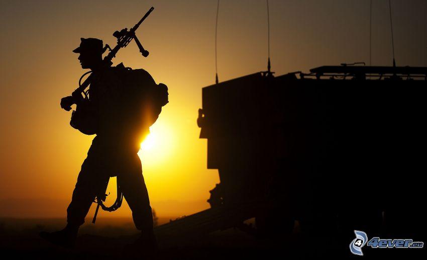 le soldat avec l'arme, coucher du soleil, silhouettes