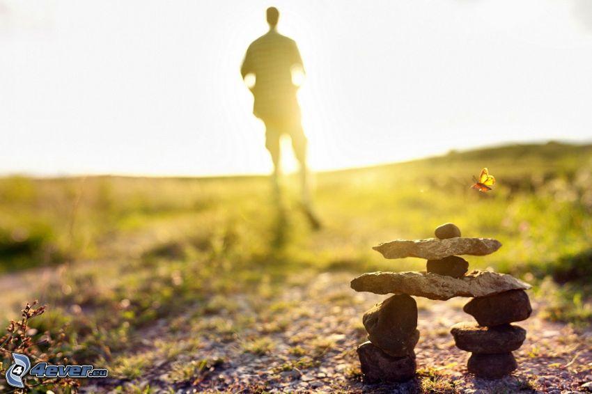 pierres, silhouette d'un homme, coucher du soleil, papillon