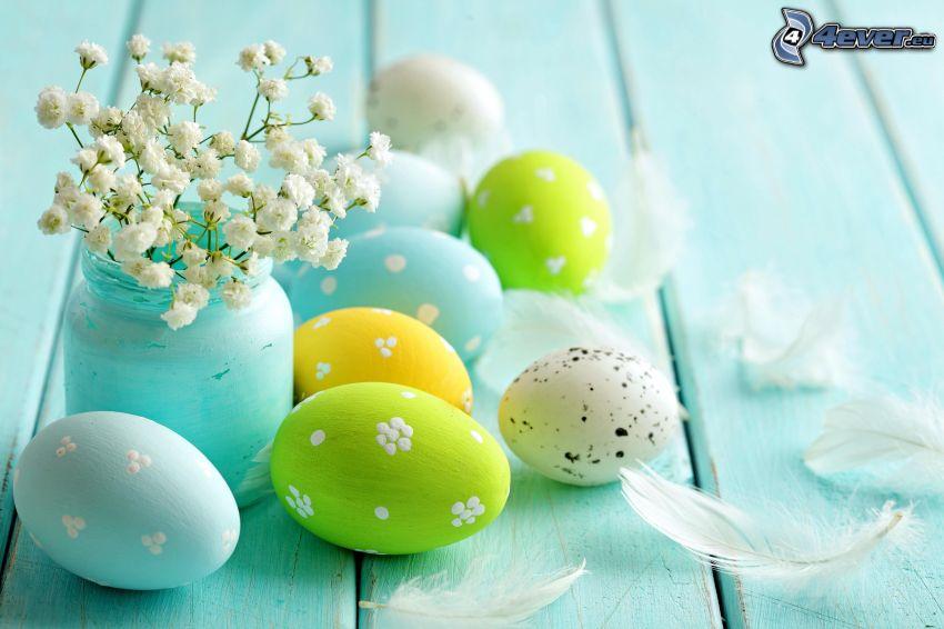 des oeufs peints, oeufs de Pâques, fleurs blanches, plumes