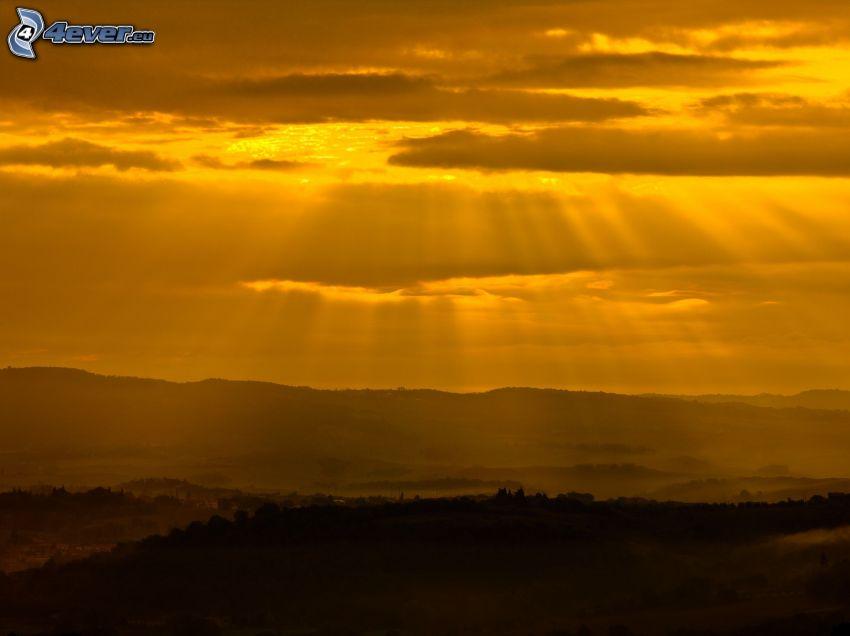 ciel jaune, montagne, rayons du soleil
