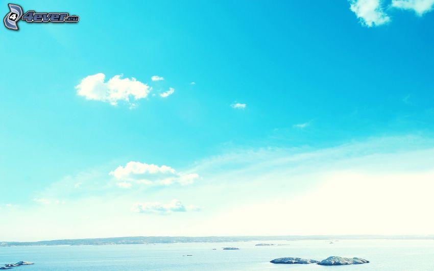 ciel bleu, roches dans la mer