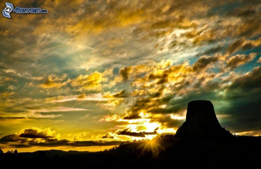 Devils Tower, rocher, silhouettes, coucher du soleil, rayons du soleil, nuages jaunes