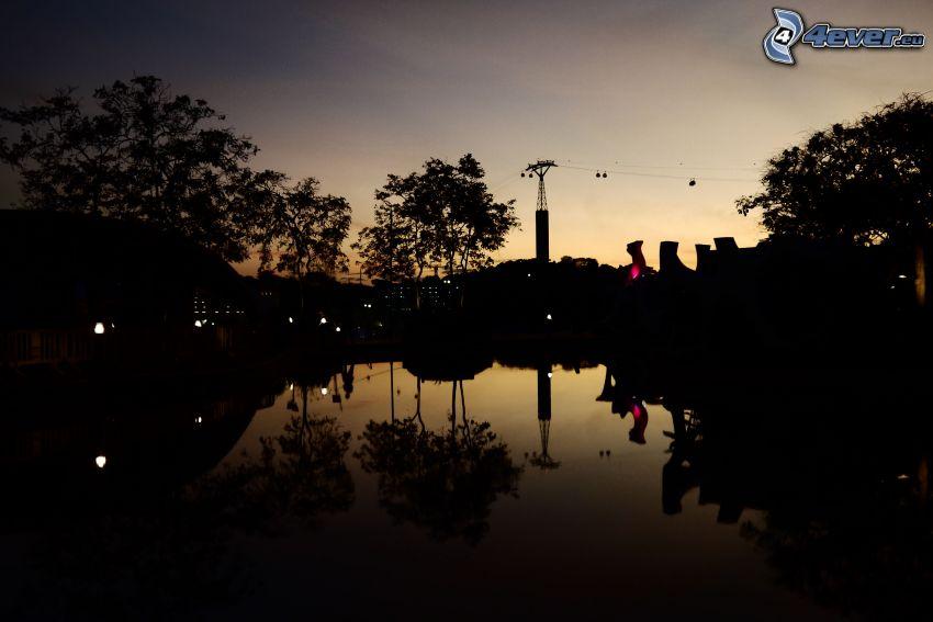 Lac calme du soir, après le coucher du soleil, silhouettes d'arbres
