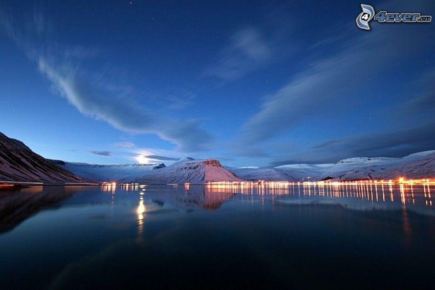 Lac calme du soir, collines enneigées, lumières