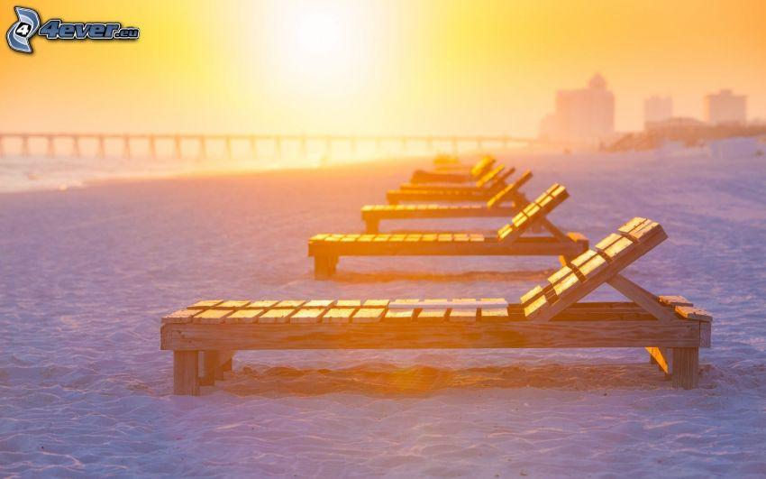 chaises longues sur la plage, coucher du soleil