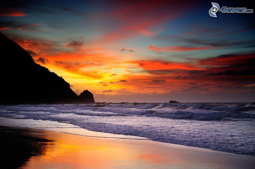 Plage au couchage du soleil, vagues sur le rivage, mer