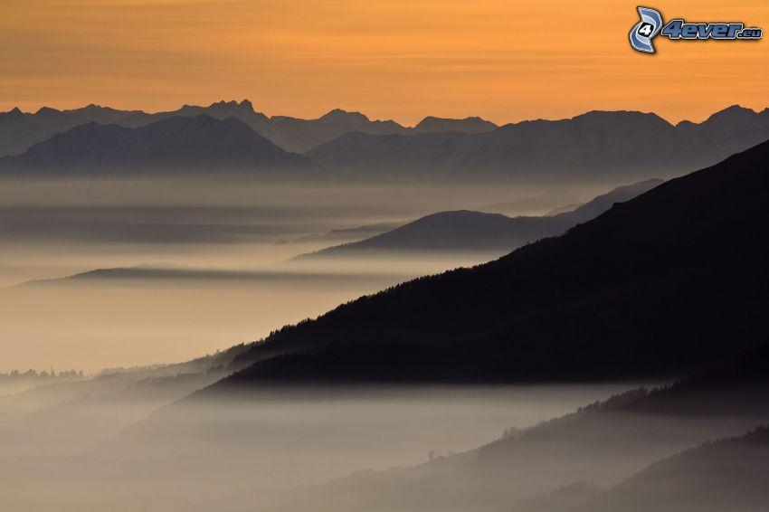 collines, brouillard au sol, coucher du soleil orange