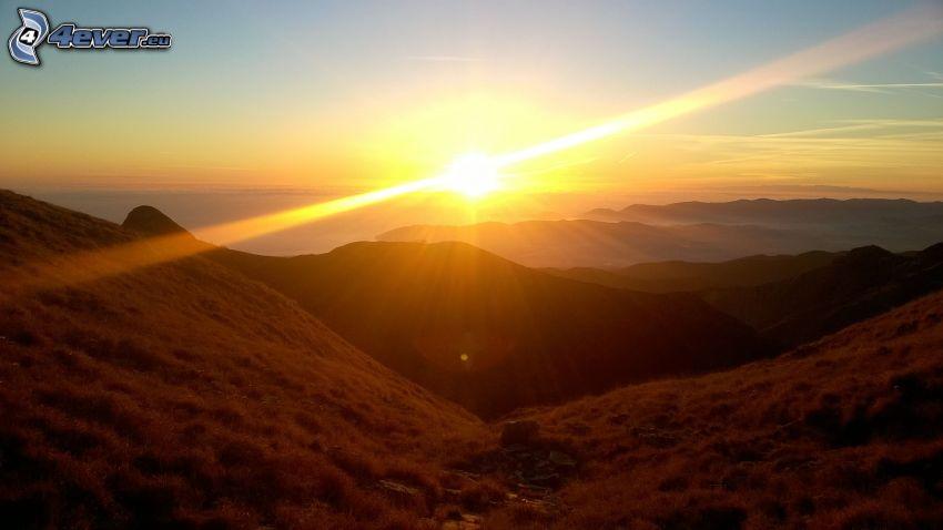 coucher du soleil derrière les montagnes