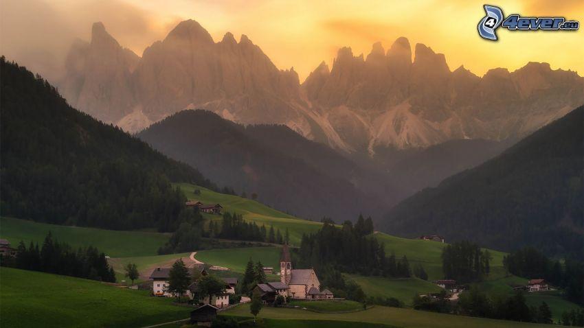Val di Funes, village, vallée, forêts et prairies, montagnes rocheuses, ciel jaune, Italie