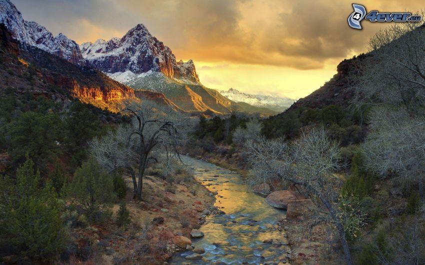 ruisseau, montagnes enneigées, arbres, coucher de soleil sur les montagnes