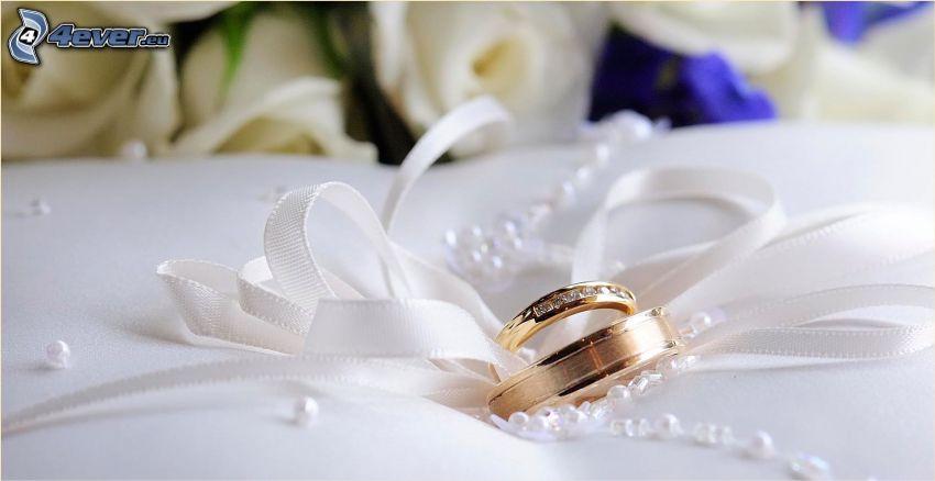 anneaux de mariage, ruban, roses blanches