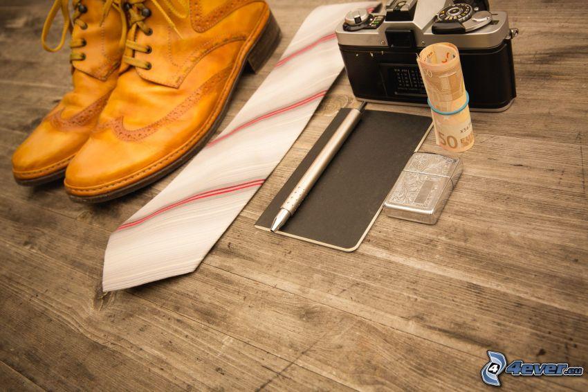 appareil photo, monnaie, cravate, chaussures, briquet, journal, stylo