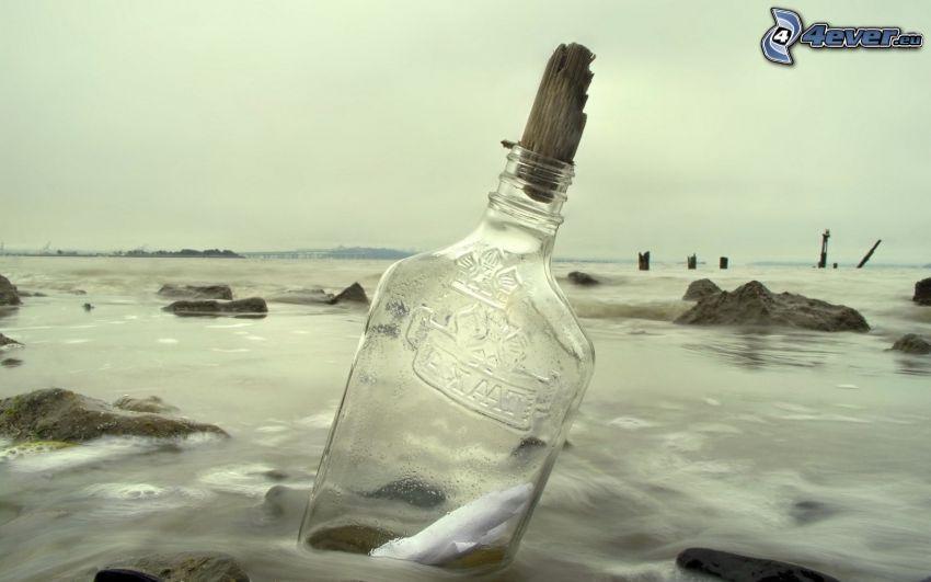 messaggio in una bottiglia, bottiglia nel mare, spiaggia di rocce