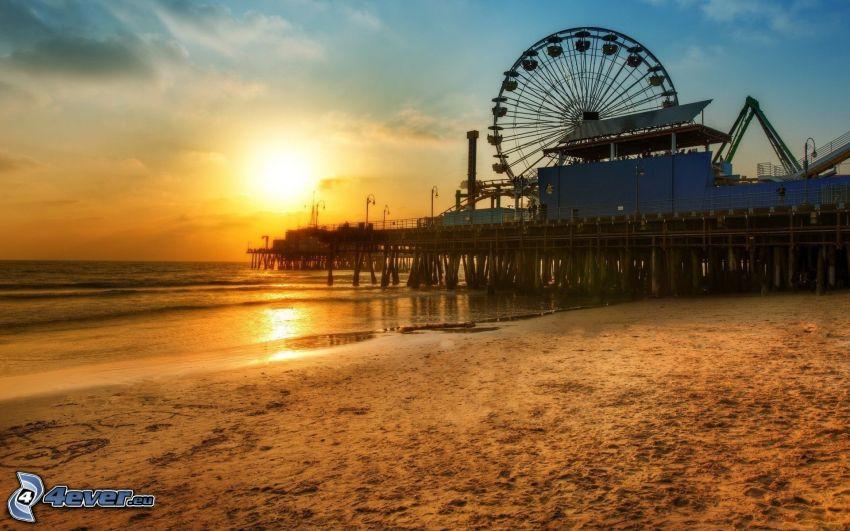Ruota gigante, tramonto sopra la spiaggia, mare, sabbia