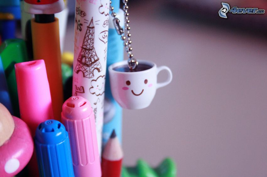 una tazza di caffè, penne, marcatori, pendente