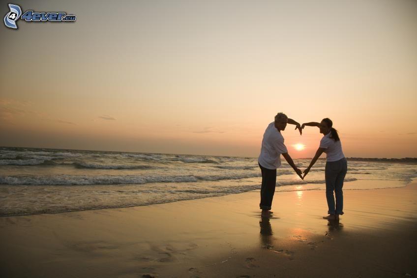 coppia al mare, cuore delle mani