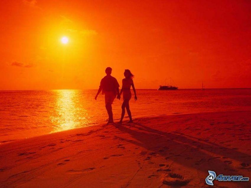 coppia al mare, tramonto arancio sopra il mare