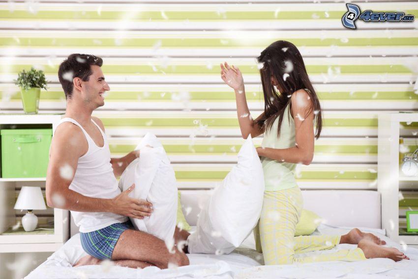 coppia su letto, gioco, cuscini, piume