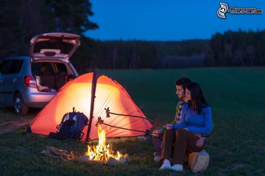 coppia sul prato, campeggio, romanticismo, arrosto sul fuoco all'aperto, fuoco, salsicciotti, tenda, sera