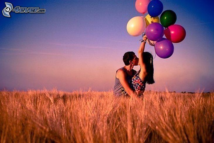 coppia sul prato, campo, palloncini, bacio, dolce abbraccio