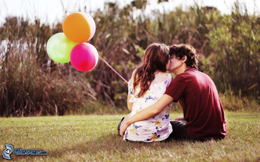 coppia sulla erba, bacio, palloncini