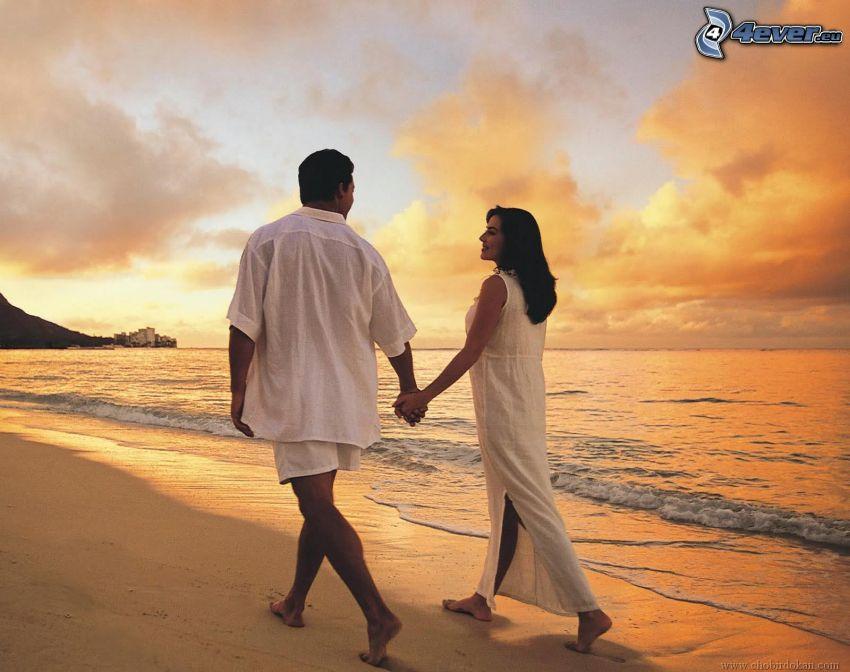 coppia sulla spiaggia, tenendosi per mano, alto mare