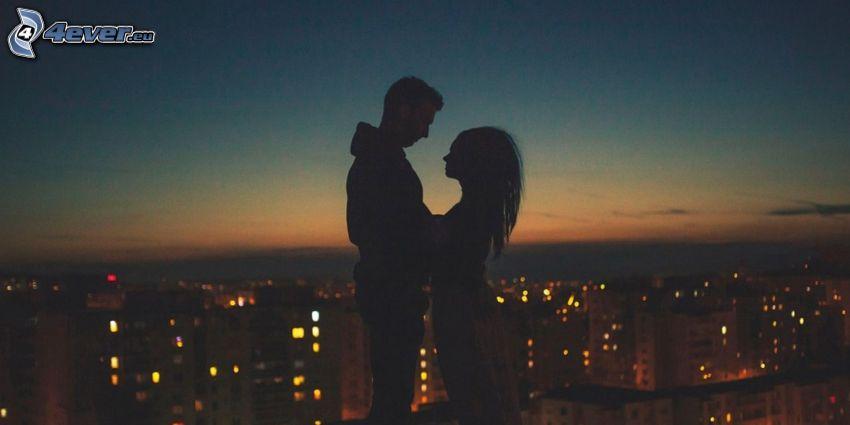 siluetta di una coppia, città notturno