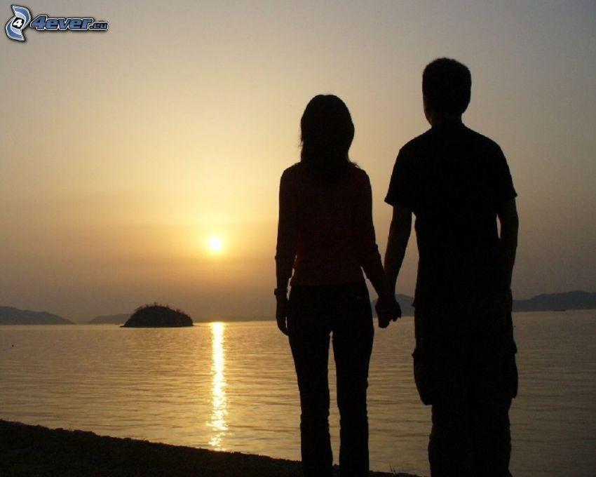 siluetta di una coppia, parco al tramonto, tramonto sopra il mare