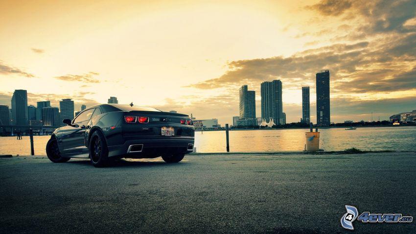 Chevrolet Camaro, grattacieli, tramonto sopra una città