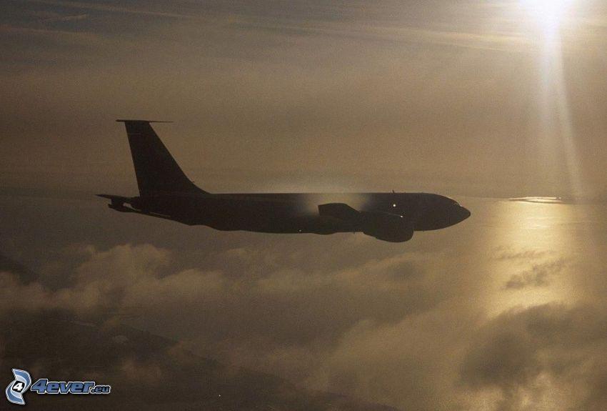 siluetta dell'aereo, sopra le nuvole, raggi del sole