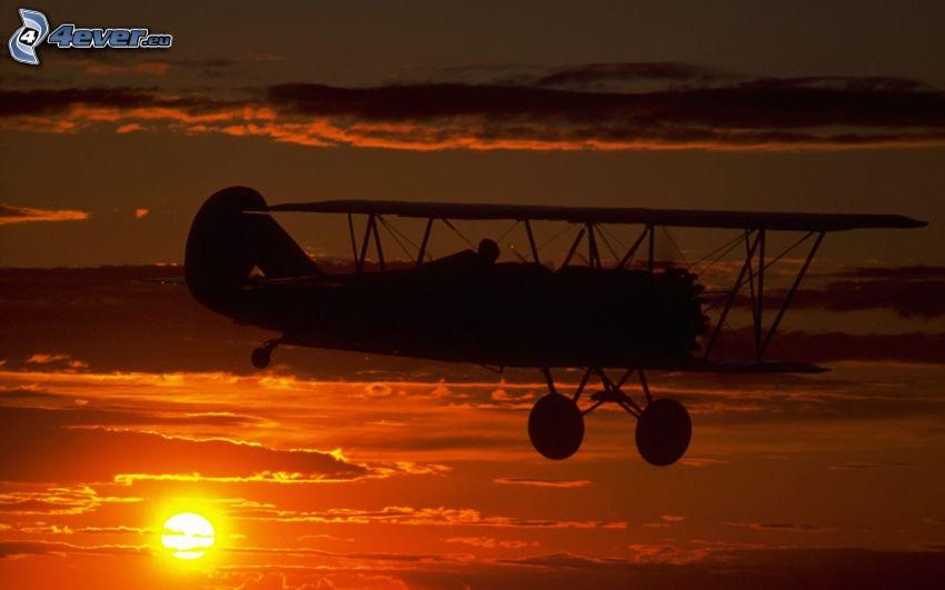 biplano, siluetta dell'aereo, tramonto