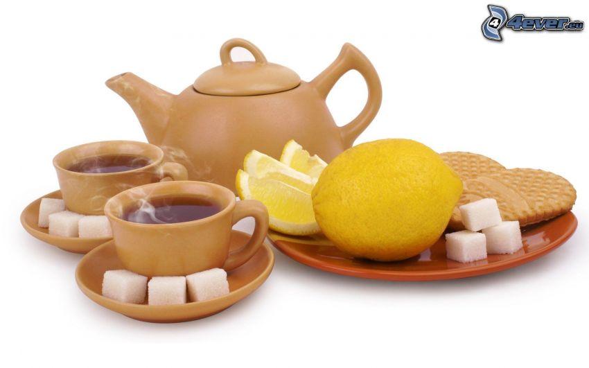 teiera, tazze, zucchero in quadretti, limone, biscotto