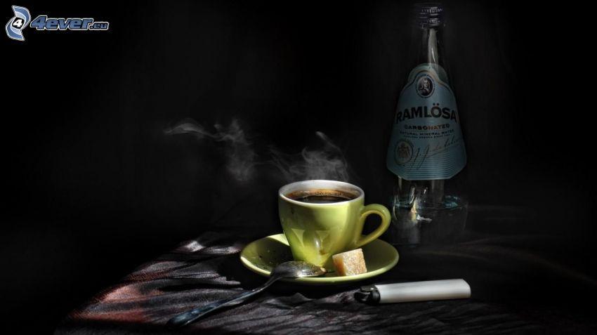 una tazza di caffè, accendino, bottiglia
