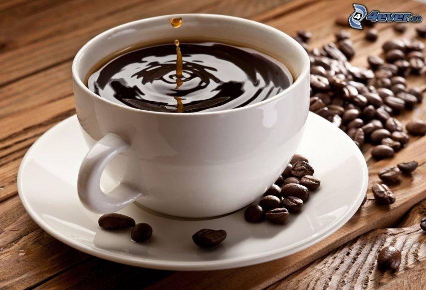 una tazza di caffè, goccia, chicchi di caffè
