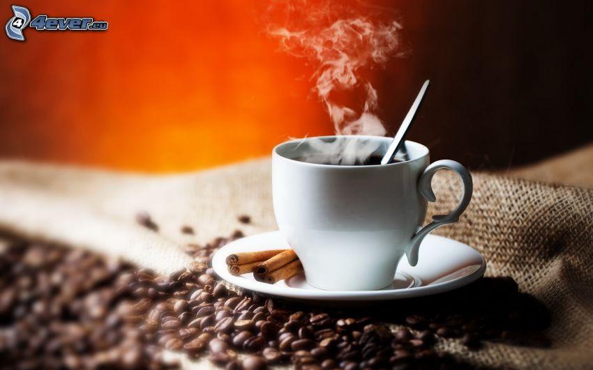 una tazza di caffè, vapore, cannella, chicchi di caffè