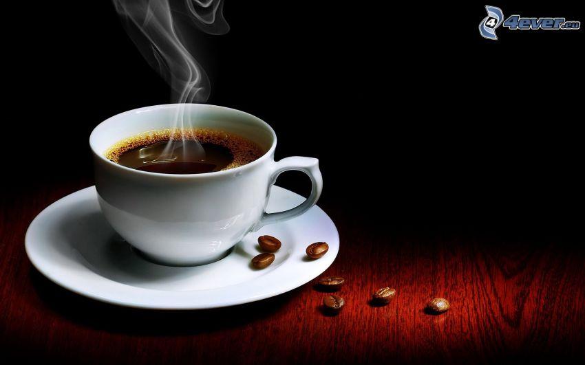 una tazza di caffè, vapore, chicchi di caffè