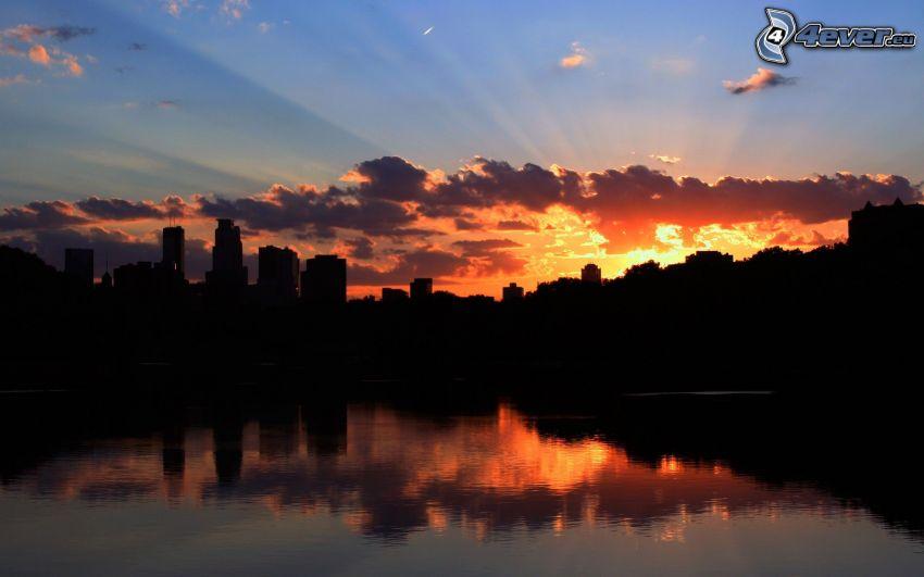 Minneapolis, siluetta di cittá, raggi del sole dietro le nuvole