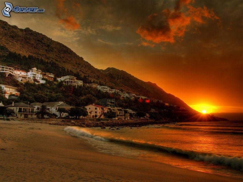 Spiaggia al tramonto, case, onde sulla costa, mare
