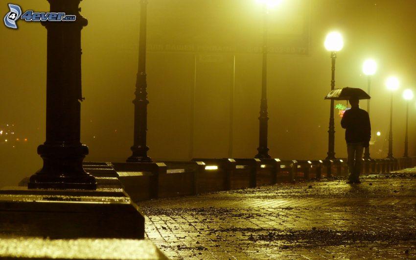 strada illuminata, uomo con l'ombrello