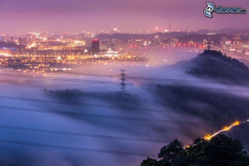 vista della città, città notturno, nebbia a pochi centimetri dal terreno, illuminazione, elettrodotto