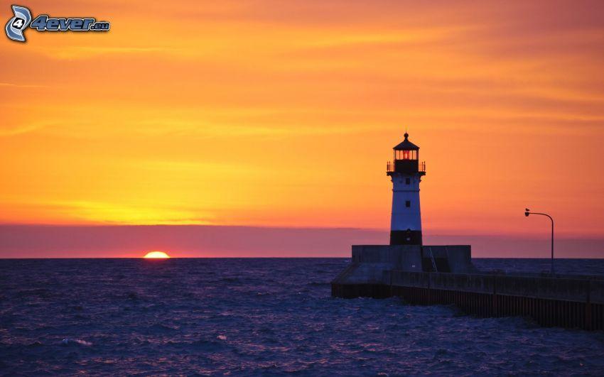 faro al tramonto, molo con un faro, mare, cielo arancione