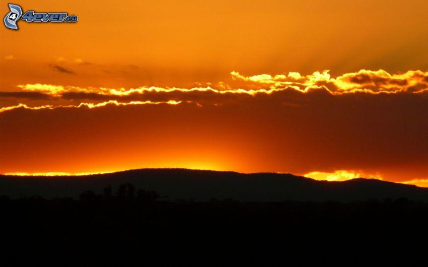 siluetta di orizzonte, colline, cielo arancione, dopo il tramonto