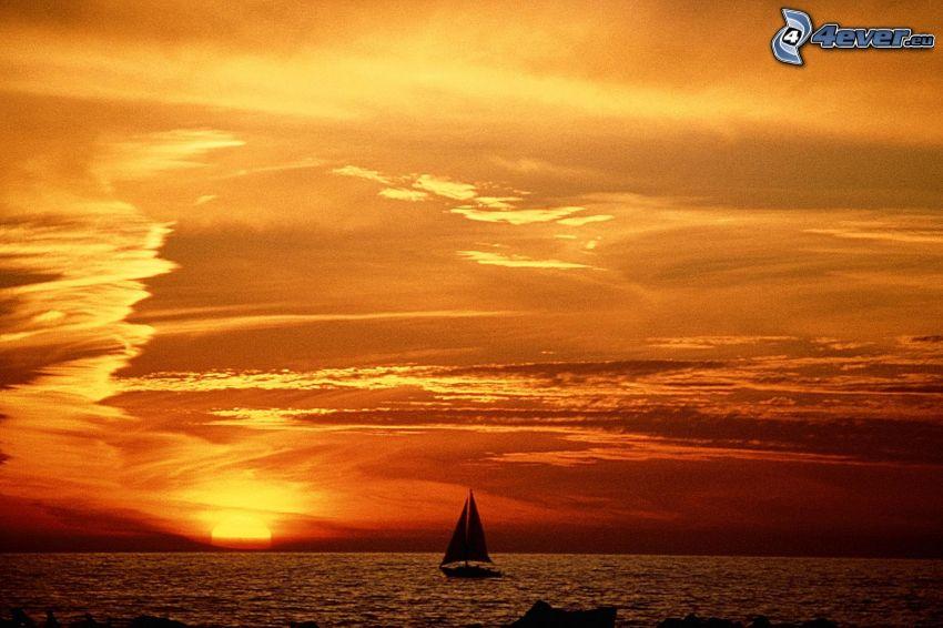 tramonto arancio sopra il mare, barca a vela