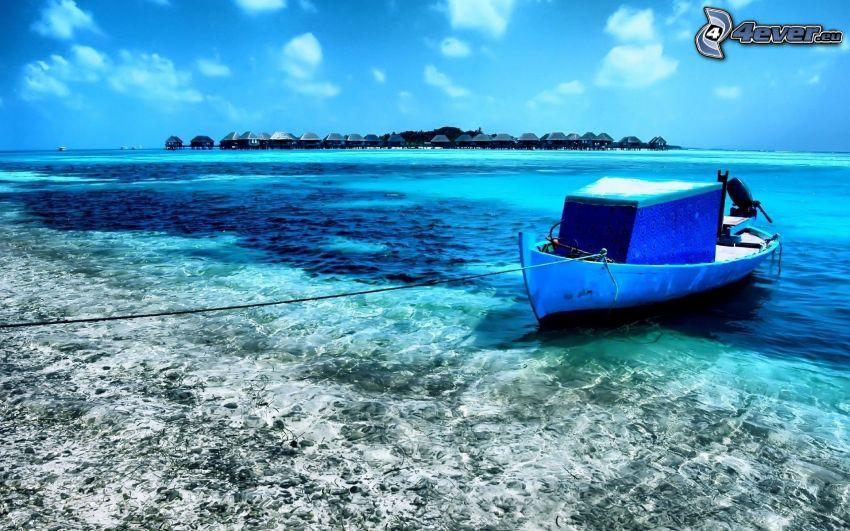 barca in riva al mare, case sull'acqua