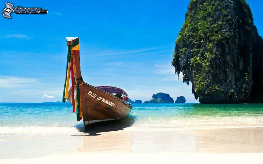 barca nella baia di Phi Phi Islands, barca alla riva, mare azzurro poco profondo, isola rocciosa, Thailandia
