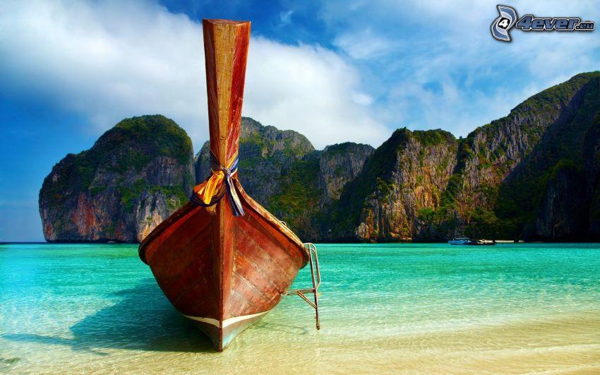 barca nella baia di Phi Phi Islands, barca alla riva, mare azzurro poco profondo, rocce, Thailandia