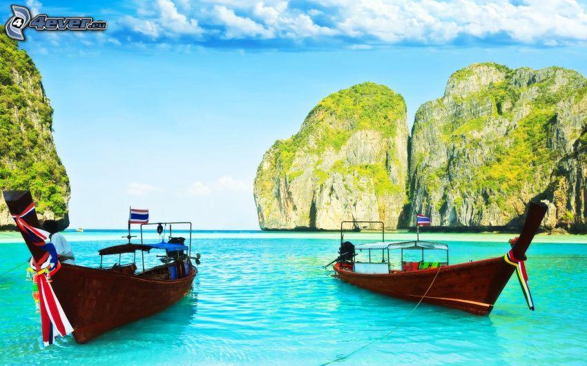 barca nella baia di Phi Phi Islands, barche vicino alla riva, mare azzurro poco profondo, isola rocciosa, Thailandia
