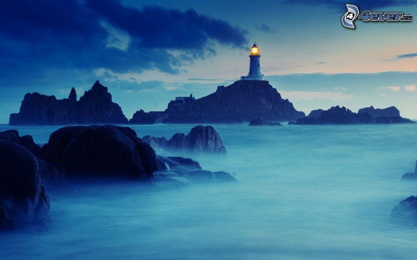 faro su una scogliera, rocce nel mare, sera