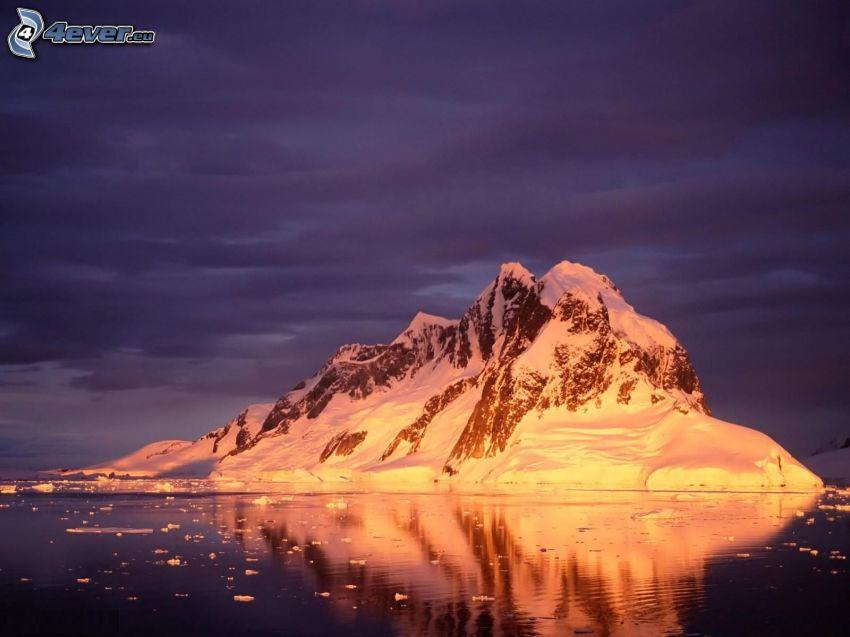isola rocciosa innevicata, mare, cielo