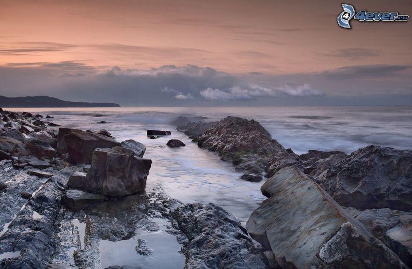 rocce nel mare, dopo il tramonto, cielo arancione